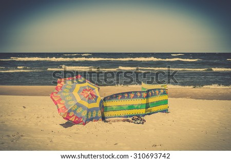 Vintage landscape with umbrella on a sandy beach by the sea under blue sky, vacation in summertime.