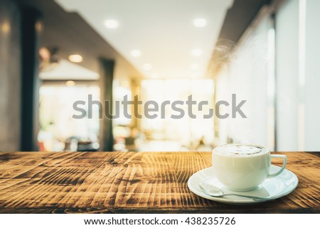 Vintage latte art with smile shape milk foam in white coffee cup on wooden table ,soft selected focus Cross process warm tone filter - stock photo