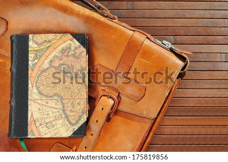 Vintage leather briefcase with old book and map  - stock photo