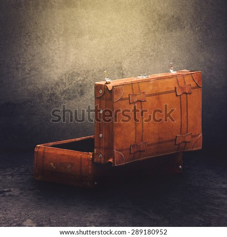 Vintage Leather Luggage Suitcase Open Ready For Packing in Concrete Room, Rear Side View, Retro Toned Effect - stock photo