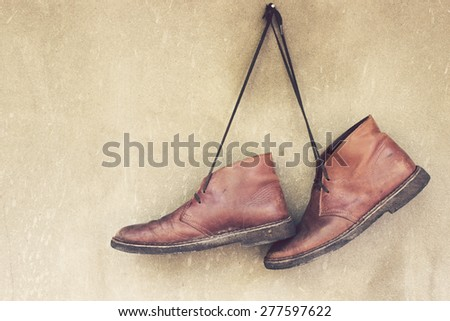 Vintage,Leather shoes hanging on the wall - stock photo