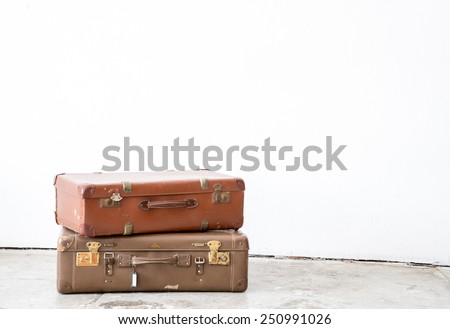 Vintage leather suitcase on white wall. - stock photo