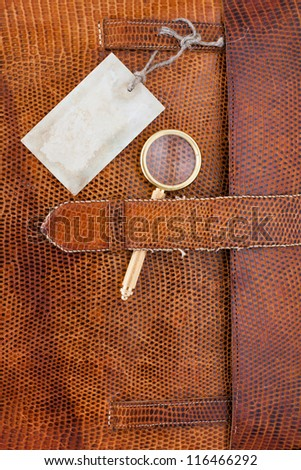 Vintage leather textured background with gift tag and magnifying glass - stock photo