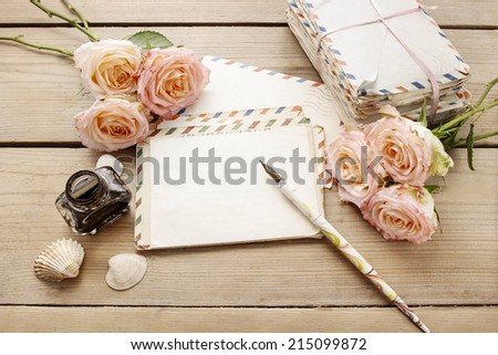 Vintage letters, roses and bottle of ink on wooden table. Top view, copy space