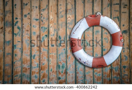 Vintage Lifebuoy Hanging On A Rustic Wooden Wall With Copy Space - stock photo
