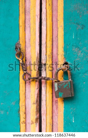 Vintage lock and chain on an old colorful wooden door - stock photo