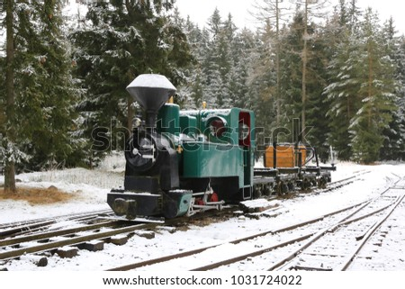 vintage locomotive train on railway in winter forest