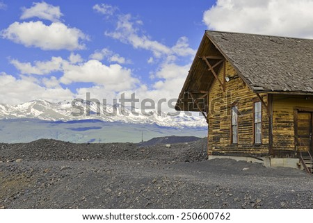 Vintage log cabin in mining town with mountain background, Rocky Mountains, Colorado - stock photo