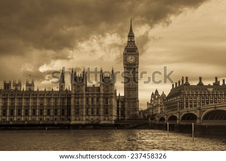 Vintage London - The Houses of Parliament and the Big Ben under thick dark clouds. - stock photo