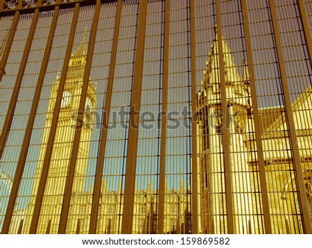 Vintage look Houses of Parliament Westminster Palace London gothic architecture seen from behind a security fence gate - stock photo