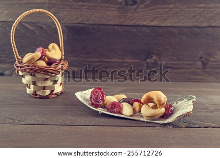 Vintage look of a mix of dried fruits on bark of birch. In the background there is a wooden small basket with dried fruits - stock photo
