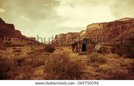 Vintage look of an old settler's cabin standing in a red rock valley of Colorado. - stock photo