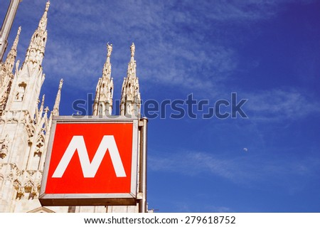 Vintage looking MILAN, ITALY - MARCH 28, 2015: Underground station sign in front of Milan Cathedral - stock photo