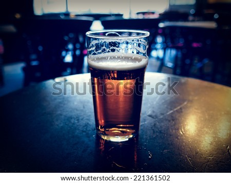 Vintage looking pint of English bitter ale in a pub - stock photo