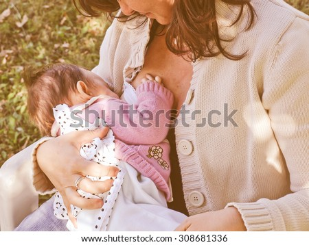 Vintage looking Pretty young brunette mum breastfeeding her baby - stock photo
