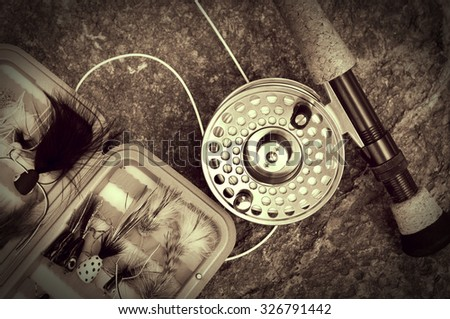 Vintage Looking Sepia Fly Fishing Rod and Tackle Box on Rocks - stock photo