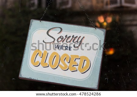 Vintage looking sorry we're closed sign in a store window