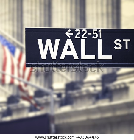 Vintage looking Wall street sign with blurred building and american flags on the background