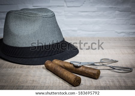 vintage luxe cigar and scissors and hat on a wood table and white brick wall background - stock photo