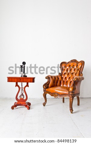 vintage luxury armchair and telephone in white room - stock photo