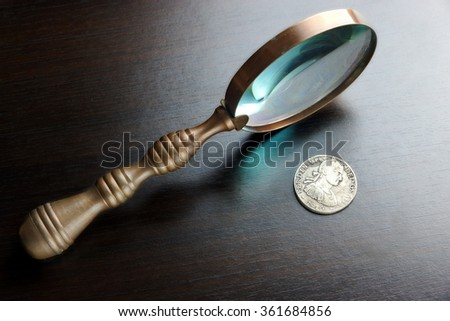 Vintage Magnifying Glass And Old Silver Coins On The Black Wood Table  In Back Light. Overhead View. Numismatic Concept - stock photo