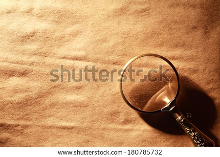 Vintage magnifying glass on nice old paper background - stock photo