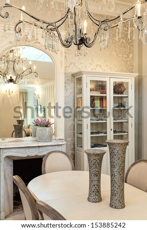 Vintage mansion - a beige dinner table with a big glass chandelier - stock photo