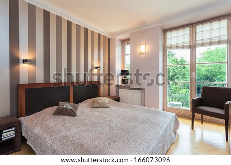 Vintage mansion - a comfy beige bed with pillows - stock photo