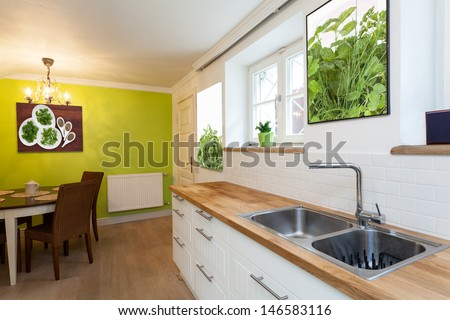Vintage mansion - a white and green kitchen with a wooden dining table - stock photo