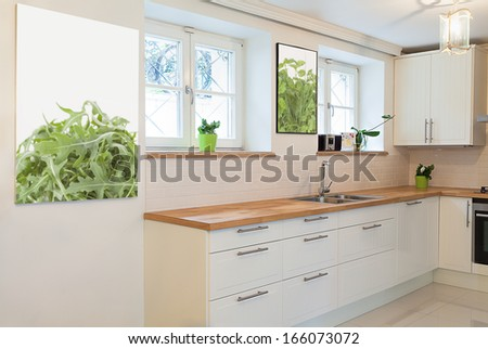 Vintage mansion - a white cooking area with pictures on walls - stock photo