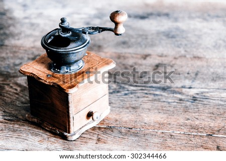 Vintage manual coffee grinder on the old wooden table - stock photo