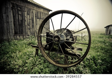 Vintage manual gras chopping machine in the misty autumn morning agaisnt barn, bleached colors - stock photo