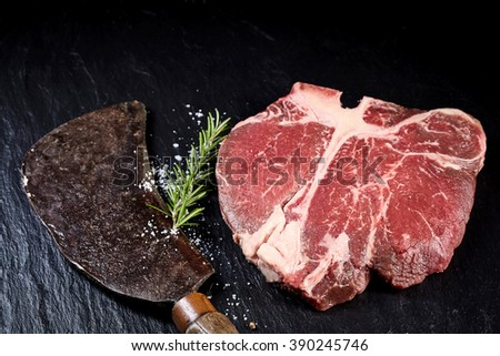 Vintage meat cleaver with a prime cut raw t-bone steak and fresh rosemary on a textured slate background in a close up high angle view - stock photo