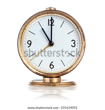 Vintage mechanical alarm clock showing eleven o'clock isolated over white - stock photo