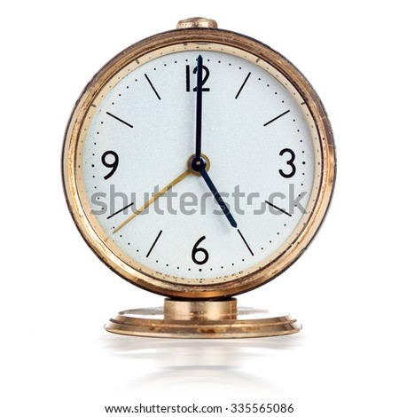 Vintage mechanical alarm clock showing five o'clock isolated over white - stock photo