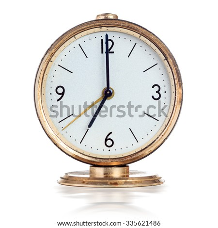 Vintage mechanical alarm clock showing seven o'clock isolated over white - stock photo