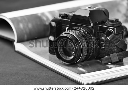 Vintage mechanical 35mm film photo camera SLR and photo book with monochrome picture. Black and white image. - stock photo