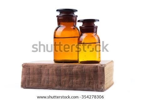 Vintage medicine pharmacy bottles with book on white background - stock photo
