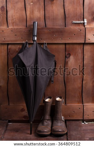 Vintage men's boots and umbrella. Men's things near the wooden fence. - stock photo