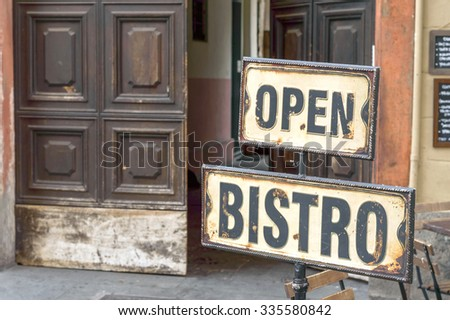 Vintage metal rusty Open Bistro sign on the street, in front of an empty cafe bar terrace and big antique wooden opened door - stock photo