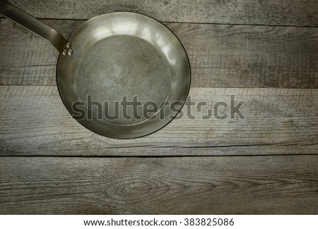 Vintage metal skillet on the old wooden background. Top  view. - stock photo