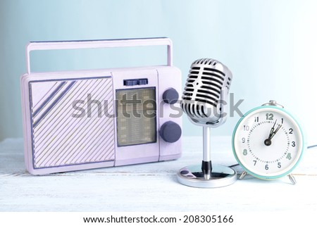 Vintage microphone,alarm clock and radio on table on light blue background - stock photo