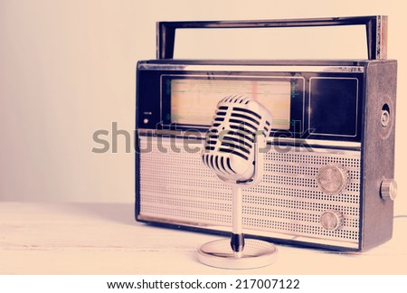 Vintage microphone and radio on table - stock photo