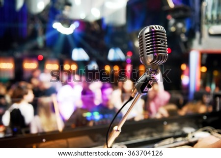 Vintage microphone in front of bright color lights inside a disco full of people. Nightlife concept.  - stock photo
