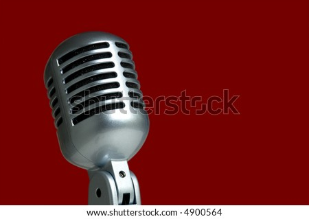 Vintage microphone on red background with plenty of space for copy
