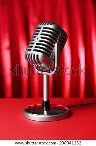 Vintage microphone on table on red cloth background - stock photo