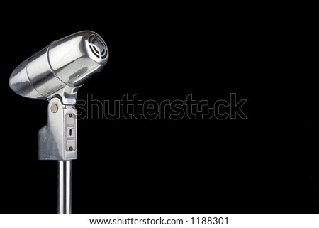 Vintage microphone over black with room for text - stock photo