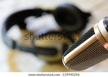 Vintage microphone with headphones in background  - stock photo