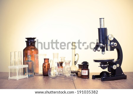 Vintage microscope and old laboratory glass retro style photo - stock photo