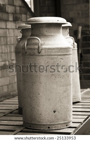 vintage milk churns photographed in black and white - stock photo